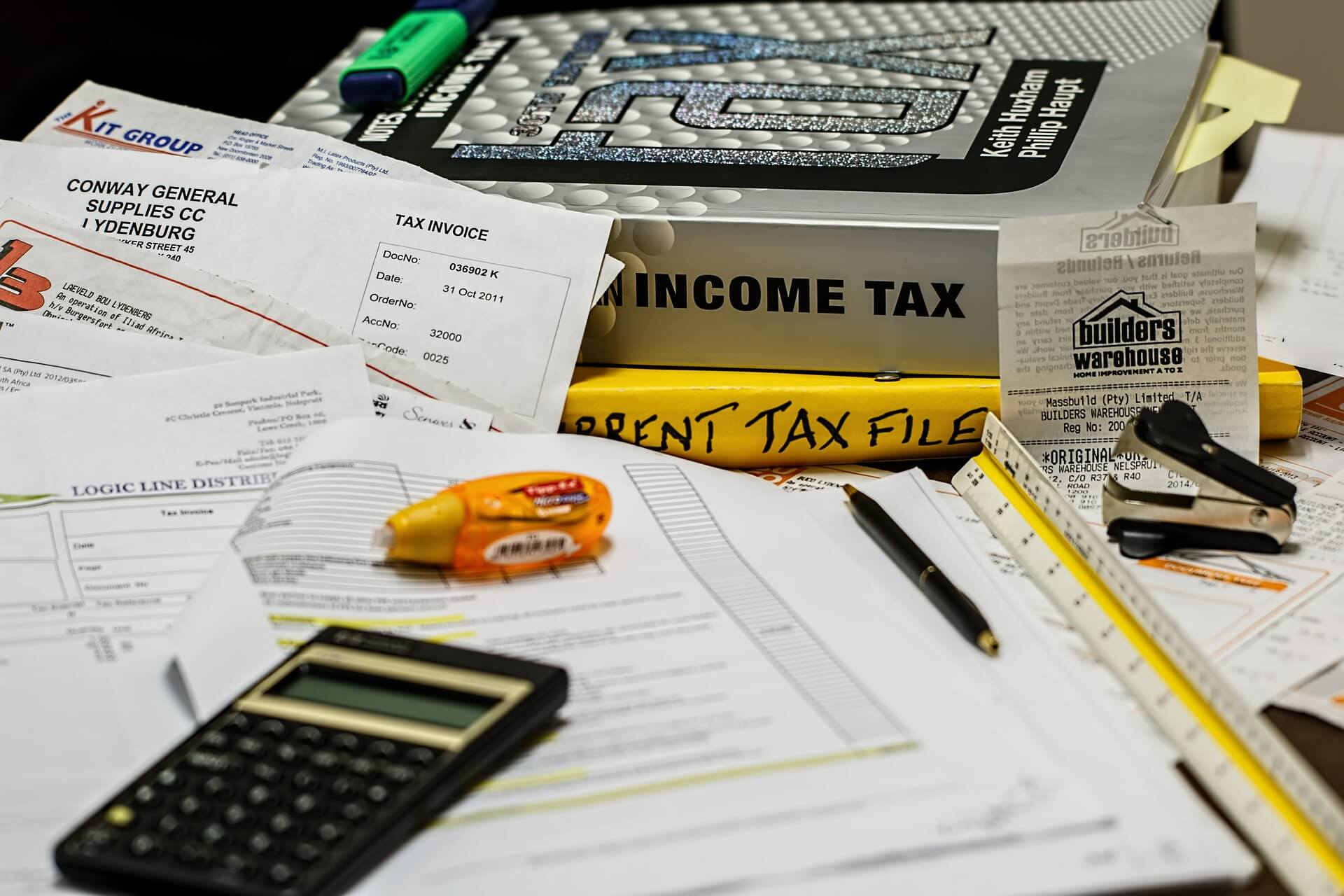 Image of papers, calculators, and books on taxes.