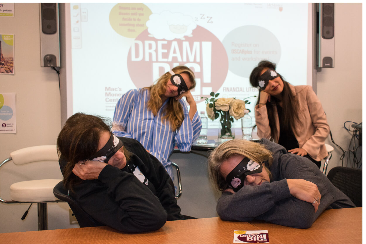 Posed image of guest speakers and Money Coaches sleeping wearing Financial Literacy Month eye masks.