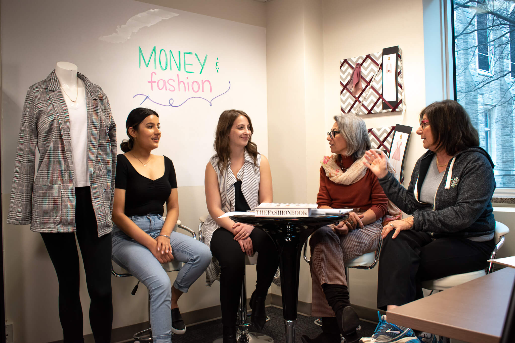 Image contains three staff members and one student speaking beside a mannequin