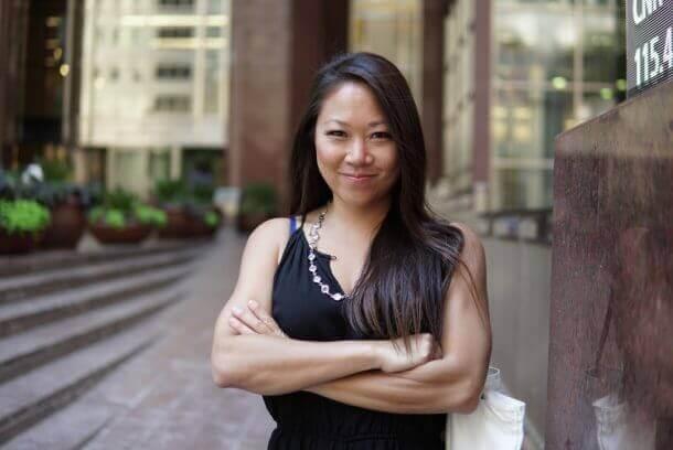 Michelle Hung, AKA the Sassy Investor, standing and smiling with her arms crossed.